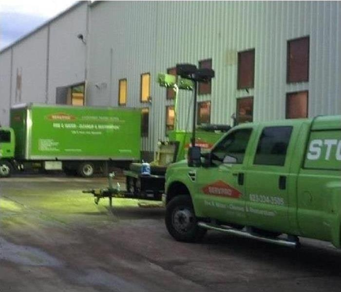 two green trucks parked outside commercial building. Concept of restoration company arrived to a damaged facility by storm