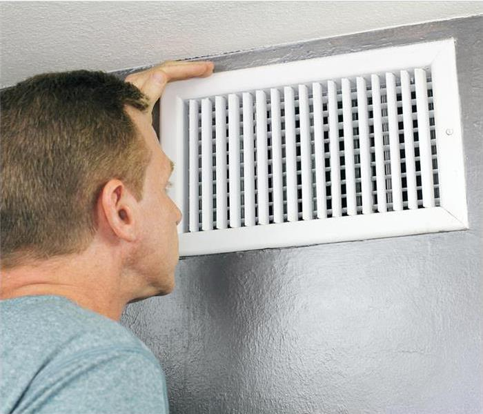 Mature man examining an outflow air vent grid and duct to see if it needs cleaning